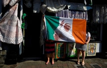 Women from a haberdashery shop hold up their new Pope Francis Ireland flag