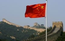 A Chinese flag flies in front of the Great Wall of China