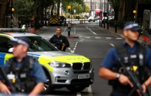 Police officers armed with riffles and bullet-proof vests stand at a cordon after a car crashed outside the Houses of Parliament in Westminster.