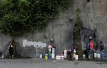 This this wide framed photograph, people fill containers with water coming from a mountain, in a road at Plan de Manzano slum in Caracas, Venezuela.