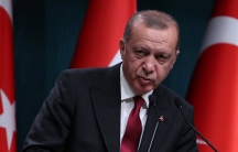 Turkish President Tayyip Erdoğan is shown speaking at a podium with Turkish flags behind him.