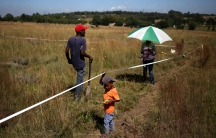 A couple and their child are seen on vacant land marked with tape in Olievenhoutbosch near Centurion, South Africa.