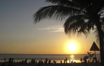 Beachgoers watch the sun set at Kuta beach in Bali, Indonesia