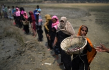 rohingya women lined up, carrying large baskets