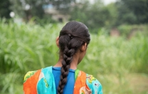 Razia, who has an intellectual disability and difficulties with speech, is depicted with her back to the camera looks out and wearing traditional patterns from India.