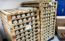 Rows of greenish-brown soap sit on wooden racks