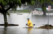 A woman rolls a bicycle through waist-high floodwaters