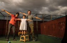 A woman, a child and man spread their arms out like airplanes on the roof of a building as they pose for a silly family photograph. Behind them are dark storm clouds.