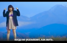 A woman wears a lacy bra and a blazer as she stands in front of a sweeping mountain vista in this screen grab from a music video. Below, a line from the song is spelled out in Kyrgyz.