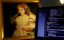 A computer screen of code is next to a copy of a painting