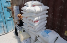 A Palestinian woman sits next to bags of flour