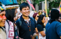 Leo Cerda is shown, adorned with indigenous wears in a crowd of activists in San Francisco.