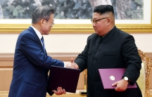 South Korean President Moon Jae-in shakes hands with North Korean leader Kim Jong-un with both carrying folders.