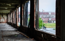 The lettering of the old Packard Plant in Detroit is seen on a brick bridge viewed through the ruins of a window in the factory.