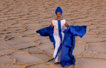 Malian singer Fatoumata Diawara is shown in a bright blue and white dress standing in the desert.