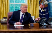 President Donald Trump is shown at his desk in the oval office talking via speakerphone.