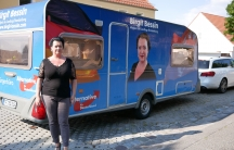 Birgit Bessin poses with a trailer bearing the logo of her party, the AfD