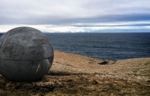 A large concrete sphere sits on a brown hill overlooking a slate blue sea.
