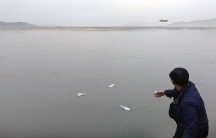 A man throws a plastic water bottle into a dark gray sea