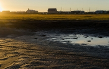 A person walks through a puddle in Shismaref, Alaska.