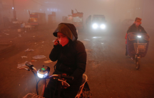 people ride motorcycles through heavy pollution in china