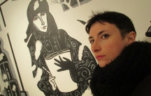 Victoria Lomasko is shown in this portrait photo with black coat standing in front of an illustrated wall.