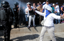 A woman wearing a blue bandana covering her face dressed in white holds her hands out to block a riot police.