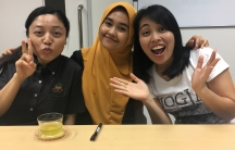 Three young women from Indonesia smile for the camera