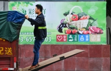 A worker wearing jeans and a reflective jacket adjusts a tarp on the back of a truck outside a warehouse of Yonghui Superstores in Chongqing, China.