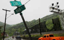 Three pick-up trucks drive down a wet road passing a street sign indicating the intersection of Coal Street and Main Street in Keystone, West Virginia, 2018.