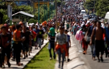 Central American migrants are shown walking on a road and sidewalk spreading the length of the highway in frame near the border with Guatemala.
