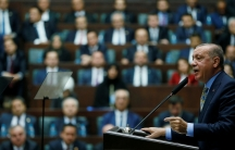 Turkish President Tayyip Erdoğan is shown at a podium addresses members of parliament in Ankara, Turkey.