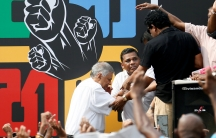 Prime Minister Ranil Wickremesinghe steps onto stage in front of colorful mural with black fist symbols