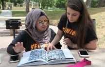Young woman sits at bench, flipping through year book, while another young woman stands next to her, leaning over to look