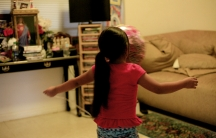 Young girl, shown from behind, with arms outstreched, in room in home