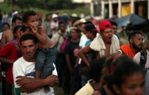 A large group of male migrants from Central America stand in line for food donations
