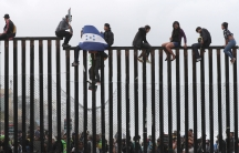 Migrants sit on top of the US-Mexico border wall.