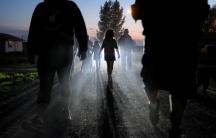 Shadowy figures walk down a dark street.