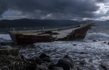 A tattered boat on the sea under stormy skies.