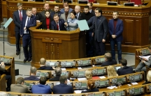 Ukrainian politician Oleh Lyashko is shown with several people behind standing at a podium pointing his finger during a parliament session.