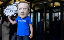 A campaigner from a political pressure group wears an oversized mask of founder and CEO ofFacebookMark Zuckerberg