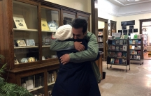 A mother and son embrace in a library.