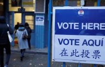 """A large blue and white sign reads """"Vote Here"""" in Spanish, Chinese and English."""