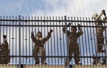 US soldiers install a razor wire fence along US-Mexico border.