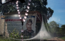 """A sign seen through a windshield says """"Welcome."""" It is marking the entrance to a FARC camp in Colombia."""