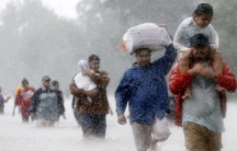 People trudge through knee-high water carrying children and bags.