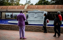 Several people including a man wearing a purple suit, look on at the stone monument for Martin Luther King, Jr.