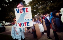 A voter carries a 'blue wave' poster at a rally