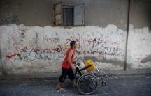 Gaza boy pushing wheelchair water