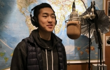 A young man is standing in front of a studio microphone